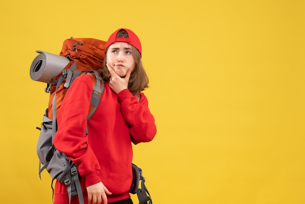 Mulher viajante pensativa de frente para a mochila vermelha em pé na parede amarela