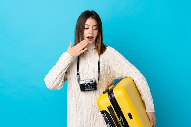 Mulher viajante segurando uma mala amarela sobre parede azul isolada