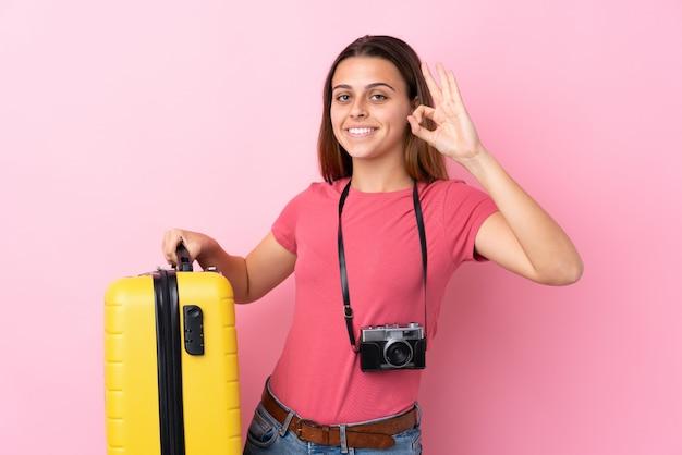 Mulher viajante sobre parede rosa isolada
