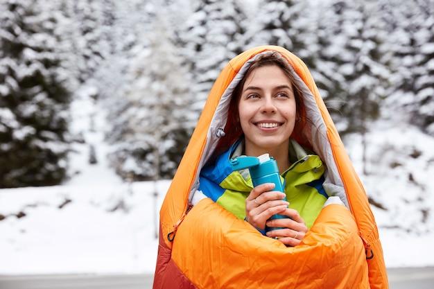 Mulher viajante sorridente caminha em uma montanha de neve, se aquece em um saco de dormir, bebe chá quente ou café