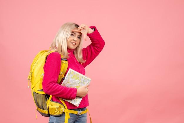 Mulher viajante sorridente com mochila segurando o mapa na parede rosa