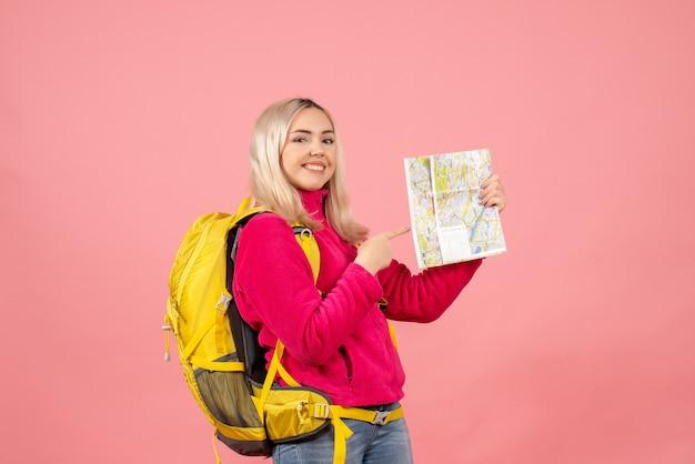 Mulher viajante sorridente de vista frontal com mochila amarela apontando para o mapa