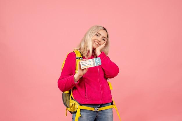 Mulher viajante sorridente de vista frontal em roupas casuais usando mochila segurando o ingresso na parede rosa