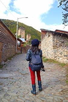 Mulher viajante subindo a colina que leva à medieval svan towerhouse, cidade de mestia, região de svaneti da geórgia