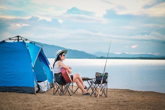 Mulher viajante tem camping e pesca perto do lago de férias.