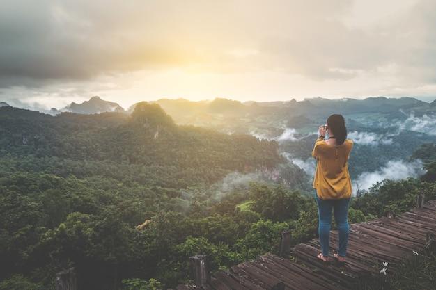 Mulher viajante tira uma foto do nascer do sol com belas cenas de montanha