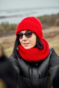 Mulher viajante tira uma selfie com o telefone dela, vestindo uma jaqueta preta e um chapéu vermelho e lenço, fundo de outono, viagem local.