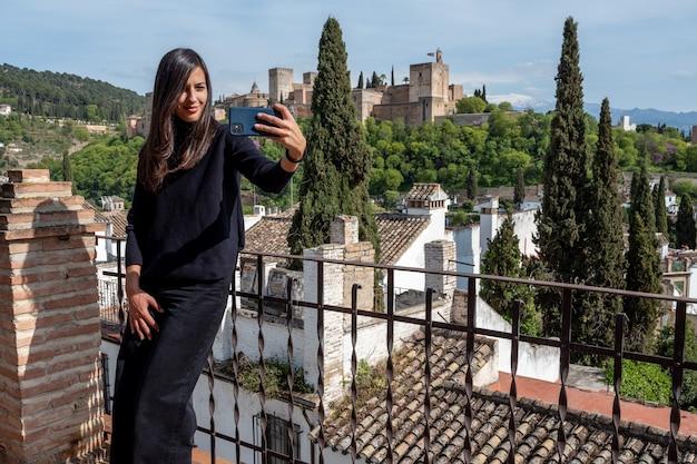 Mulher viajante tirando uma selfie no smartphone em pé no terraço contra a fortaleza de alhambra em granada, espanha