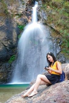 Mulher viajante tirar foto cachoeira por sua câmera