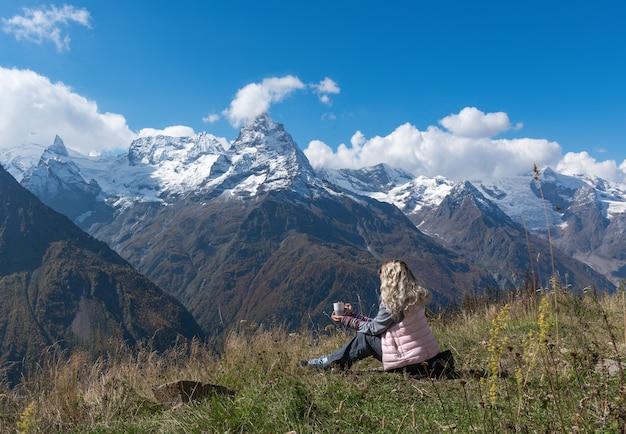 Mulher viajante toma café com vista para a paisagem montanhosa