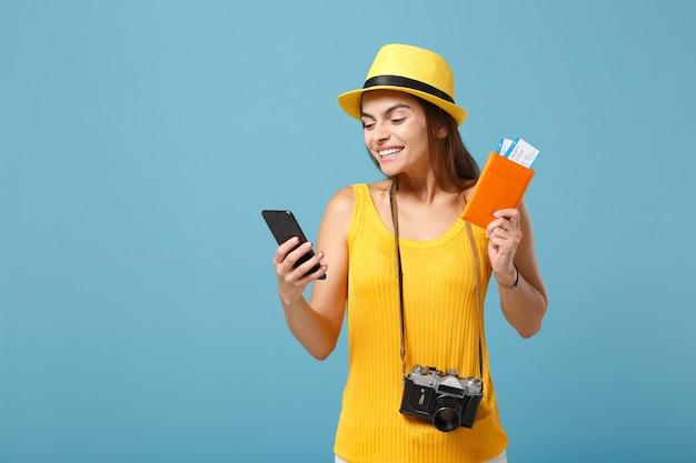 Mulher viajante turista com chapéu amarelo com roupas casuais segurando a câmera do celular do bilhete azul