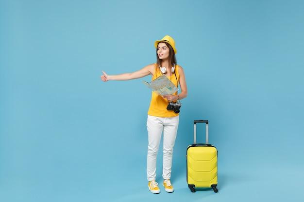 Mulher viajante turista com chapéu amarelo roupas casuais segurando uma câmera fotográfica de mala de mapa em azul