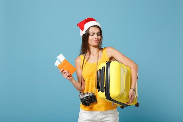Mulher viajante turista com chapéu de papai noel, roupas casuais amarelas segurando a câmera da bolsa de ingressos azul