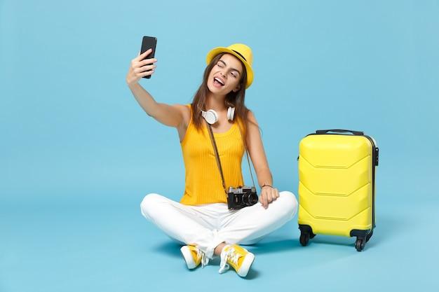 Mulher viajante turista em roupas casuais amarelas, chapéu com câmera fotográfica de mala em azul