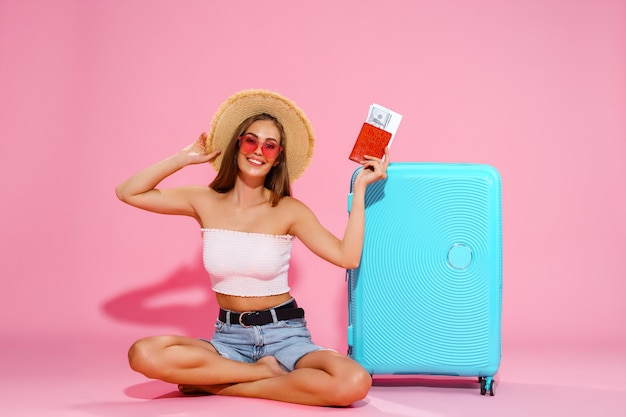 Mulher viajante turística com passaporte e passagens mala calção branco chapéu de palha