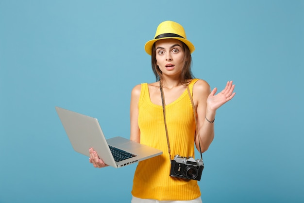 Mulher viajante turística com roupas de verão amarelas, chapéu com computador portátil na cor azul