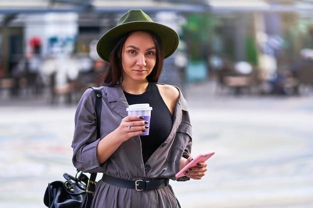 Mulher viajante usando chapéu de feltro e macacão com uma mochila segurando um copo de papel