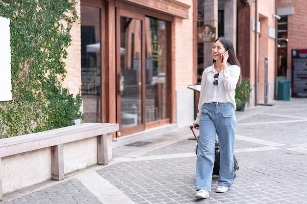 Mulher viajante usando smartphone e arrastando mala preta