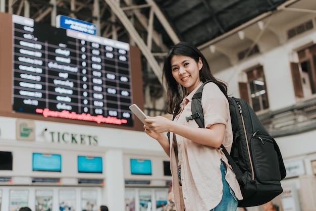 Mulher viajante usar smartphone frente da bilheteria