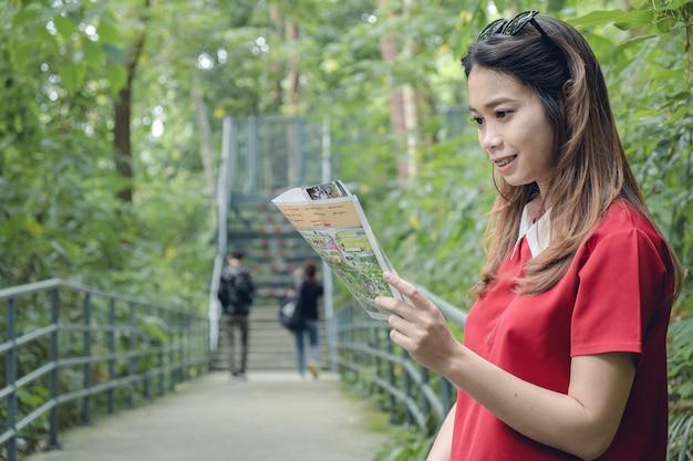 Mulher viajante verifica o mapa para encontrar direções, conceito de viagens