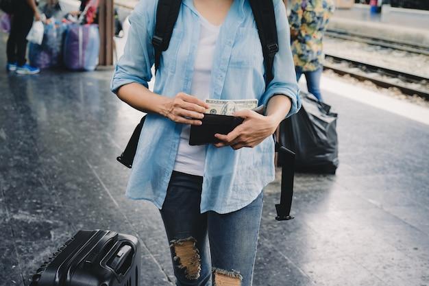 Mulher viajar com mochila dólares americanos dinheiro na carteira, plano financeiro para o turismo.