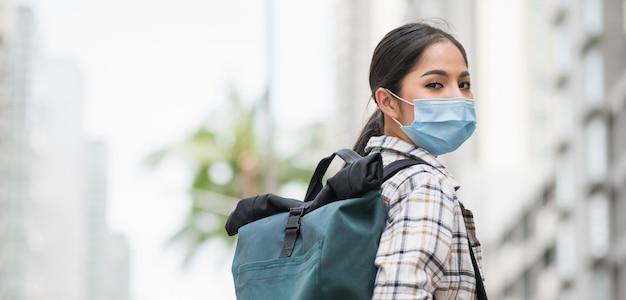 Mulher viajar de férias com mochila e usando o vírus de máscara de proteção.