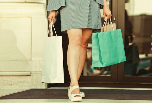 Mulher viciada em compras com pernas triplas e sacolas de papel para passeios de compras pela cidade