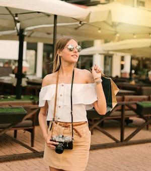 Mulher viciada em compras em roupas elegantes com câmera retro