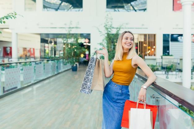 Mulher viciada em compras jovem alegre segurando sacos de papel com compras e sorrindo, olhando para a câmera dançando no centro comercial. senhora feliz se divertindo na sexta-feira negra, pula de alegria no shopping