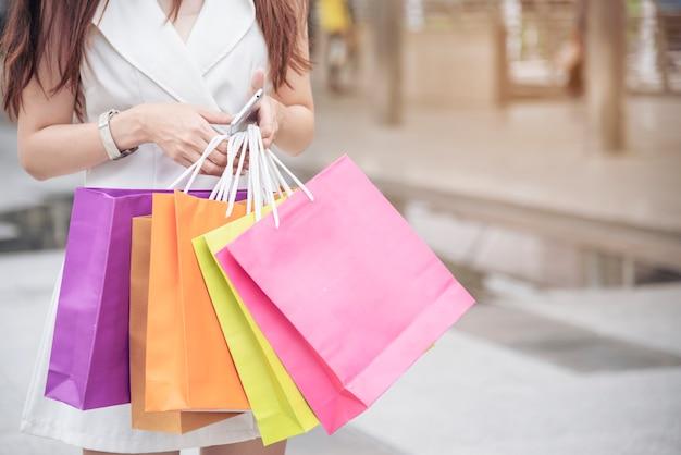 Mulher viciada em compras, segurando sacolas de compras, dinheiro, cartão de crédito em shopping centers