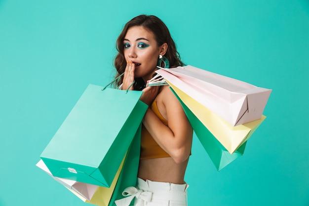 Mulher viciada em compras, vestindo moda estilo segurando sacolas de papel colorido com compras