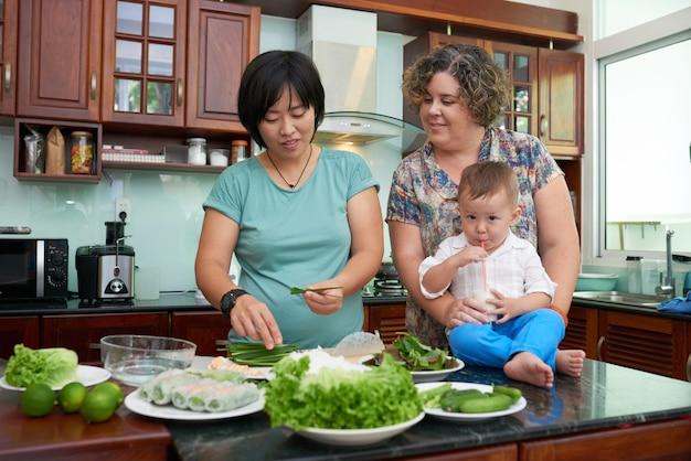 Mulher vietnamita cozinhando rolinhos primavera tradicionais para a esposa e o filho