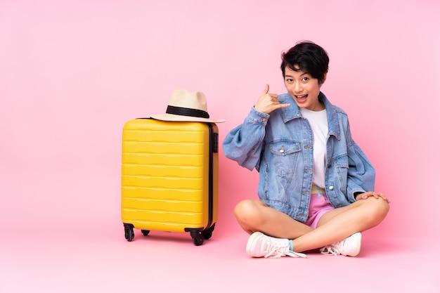 Mulher vietnamita do jovem viajante com mala sentado no chão parede rosa fazendo gesto de telefone.