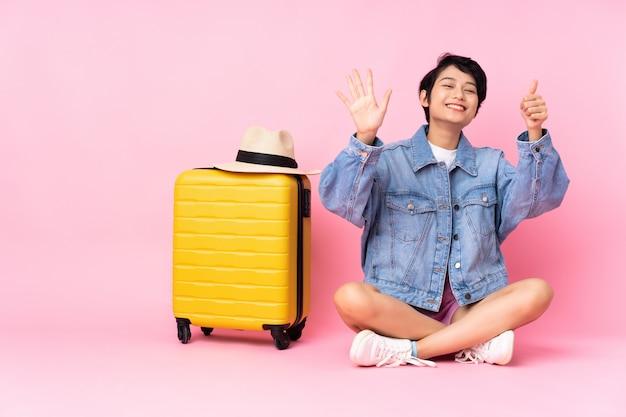 Mulher vietnamita jovem viajante com mala sentada no chão parede rosa isolada, contando seis com os dedos