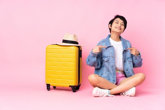 Mulher vietnamita jovem viajante com mala sentada no chão sobre parede rosa isolada, orgulhosa e satisfeita