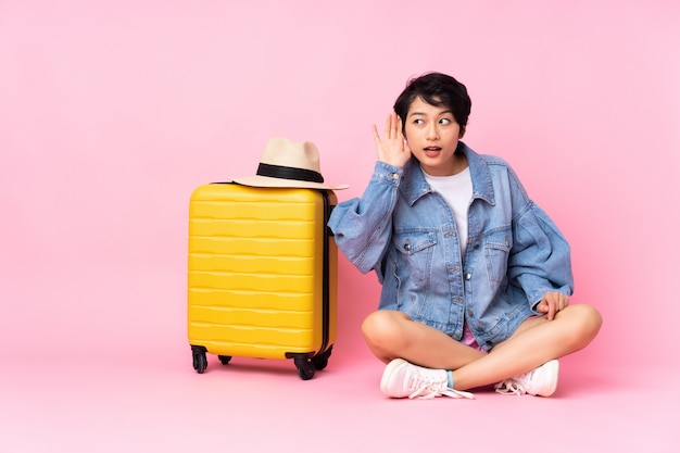 Mulher vietnamita jovem viajante com mala sentada no chão sobre parede rosa isolada, ouvindo algo, colocando a mão na orelha