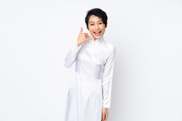 Mulher vietnamita nova com o cabelo curto que veste um vestido tradicional sobre o gesto de factura branco isolado do telefone. ligue para mim de volta