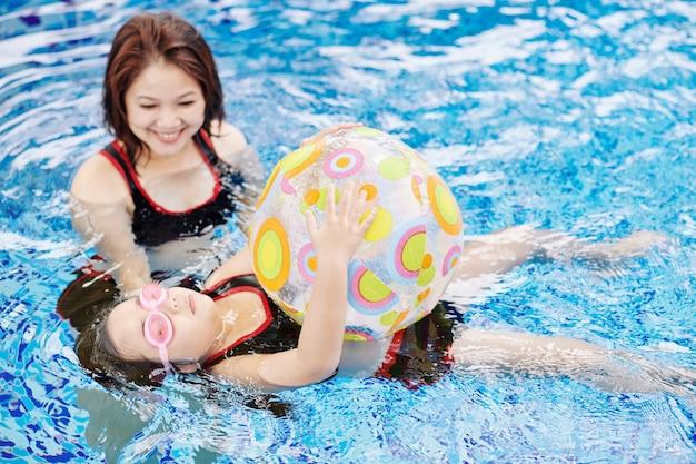 Mulher vietnamita positiva controlando a filha, aprendendo a nadar de costas com uma bola inflável