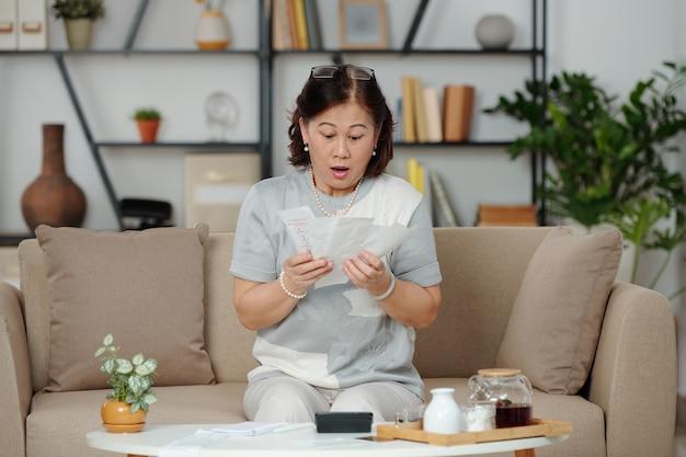 Mulher vietnamita sênior chocada e chocada olhando para muitas contas que precisa pagar