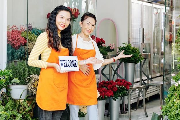 Mulher vietnamita sênior com sua filha adulta segurando uma placa de boas-vindas ao convidar clientes na floricultura da família