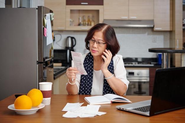 Mulher vietnamita sênior séria sentada à mesa da cozinha, verificando contas e recibos e falando ao telefone