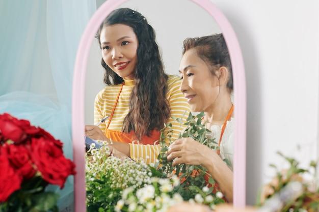 Mulher vietnamita sênior sorridente e sua filha adulta administrando o negócio da família e fazendo buquê para o cliente, reflexo no espelho