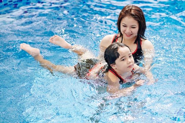 Mulher vietnamita sorridente ensinando a filha a nadar na piscina