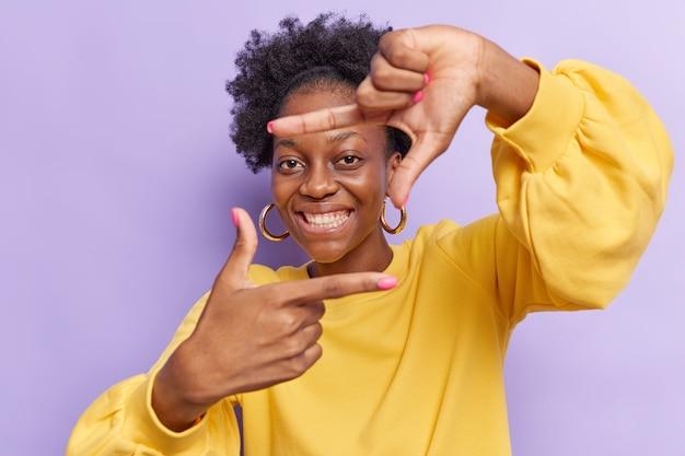 Mulher visa apenas o sucesso faz armações de mão pesquisas ângulos perfeitos sorrisos amplamente usa suéter amarelo isolado no roxo