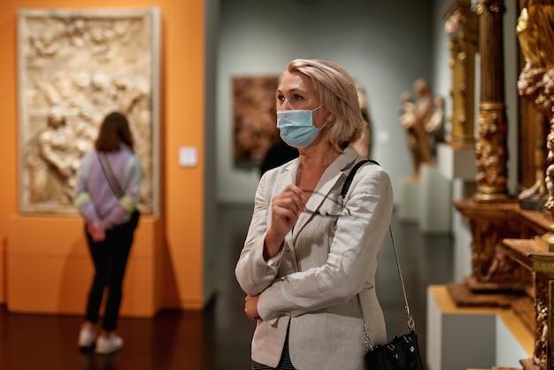 Mulher visitando museu usando máscara antivírus