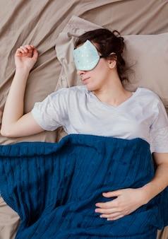 Mulher vista de cima com máscara de dormir dormindo