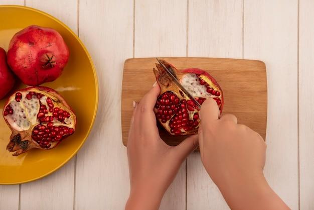 Mulher vista de cima cortando meia romã em uma tábua com um todo em um prato em uma parede branca