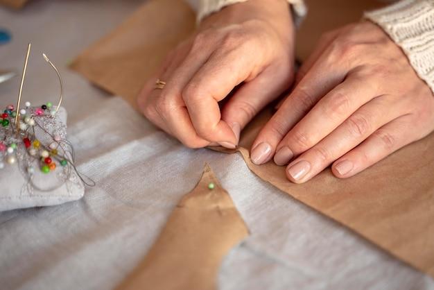 Mulher vista de cima costurando com agulha e linha