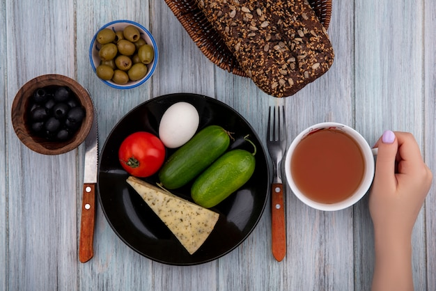 Mulher vista de cima segurando uma xícara de chá com queijo, pepinos, tomate e ovo em um prato com azeitonas pretas e verdes em um fundo cinza