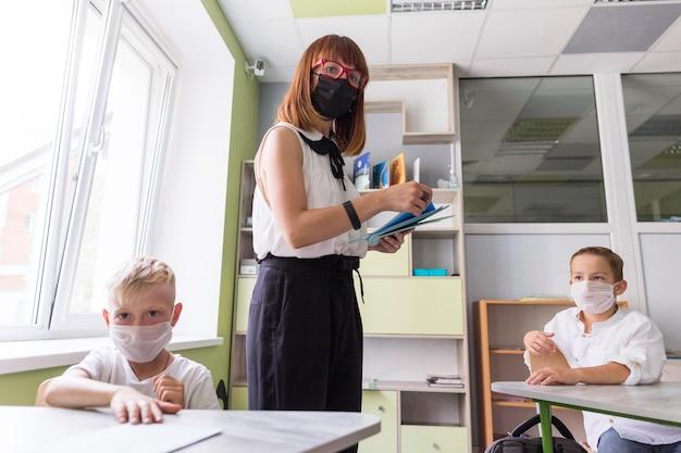 Mulher vista de frente usando uma máscara médica em sala de aula ao lado de seus alunos